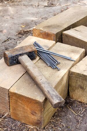 Vintage old rusty hammer and nails lying on wooden bars on the ground at a house construction site