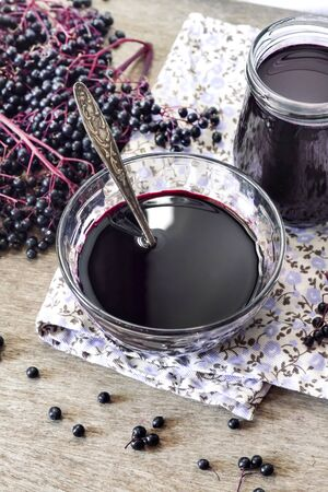 Homemade black elderberry syrup in glass bowl and jar and bunches of black elderberry in background Stock fotó