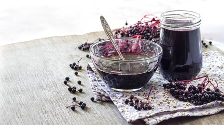 Homemade black elderberry syrup in glass bowl and jar and bunches of black elderberry in background. Copy space Stock fotó