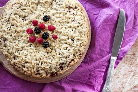 Homemade berry shortcrust pie with crumble on wooden board and purple cloth. Flat lay, top view Stock Photo - 129468614