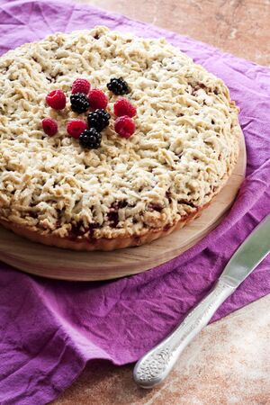 Homemade berry shortcrust pie with crumble on wooden board and purple cloth Stock Photo - 129468615
