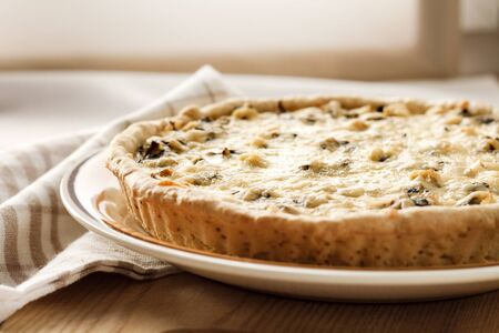 Chicken tart with mushrooms and cheese on a plate Foto de archivo - 129860727