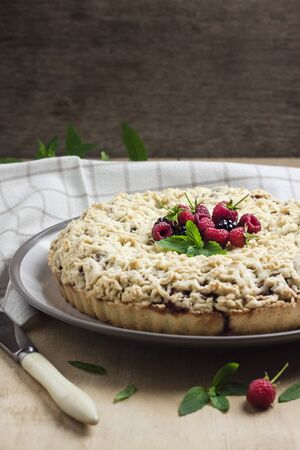 Homemade berry shortcrust pie with crumble on a plate on wooden table. Copy space Stock fotó
