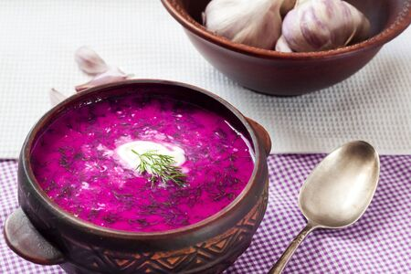 Holodnik - traditional Lithuanian (Russian, Ukrainian, Belorussian, Polish) cold beetroot soup with cucumber, boiled eggs and greens in rustic bowl Фото со стока