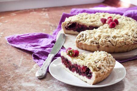Homemade berry shortcrust pie with crumble on wooden board and purple cloth Stock fotó