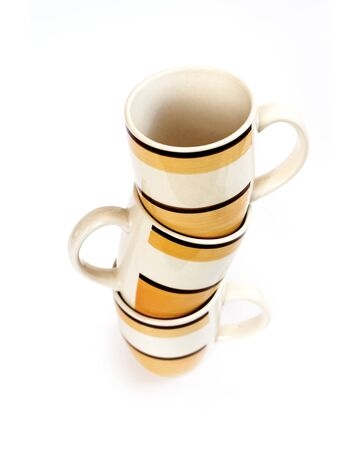 Stack of three mugs isolated on white background with clipping path