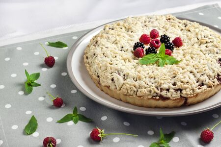 Homemade berry shortcrust pie with crumble on plate and grey dotted cloth Stock Photo