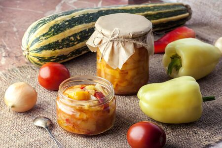 Homemade preserving. Zucchini and bell pepper salad in glass jar with ingredients on background