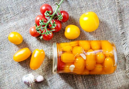 Glass jars with homemade red and yellow pickled tomatoes, sealed with metal lid. Top view, flat lay 스톡 콘텐츠