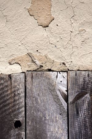 Old cob wall with cracked surface and old wooden boards. Vintage background for design purposes Standard-Bild - 133704105