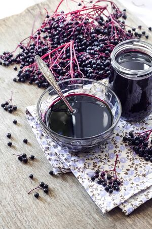Homemade black elderberry syrup in glass bowl and jar and bunches of black elderberry in background 스톡 콘텐츠
