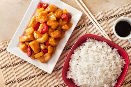 Sweet and sour chicken with bell pepper and pineapple. Flat lay, top view Фото со стока