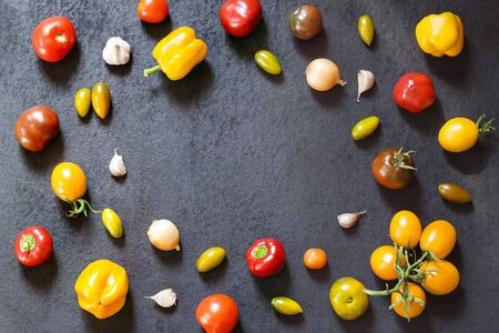 Assortment of colorful fresh vegetables on black background. Flat lay, top view.