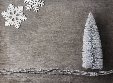 Christmas composition with silver Christmas tree and snowflakes on wooden background. Christmas, new year concept. Flat lay, top view, copy space