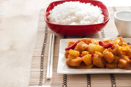Sweet and sour chicken with bell pepper and pineapple. White rice on background. Copy space Foto de archivo - 135500849