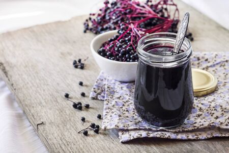 Homemade black elderberry syrup in glass jar and bunches of black elderberry in background, copy space