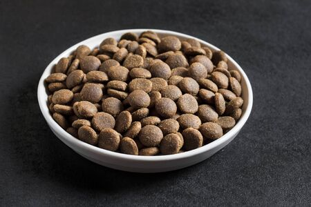 Dry pet food in a white ceramic bowl on black background.