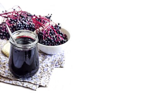 Homemade black elderberry syrup in glass jar and bunches of black elderberry in background. Copy space
