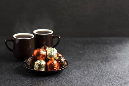 Chocolate candies wrapped in multicolored foil on a plate and two cups of hot coffee on black background with copy space