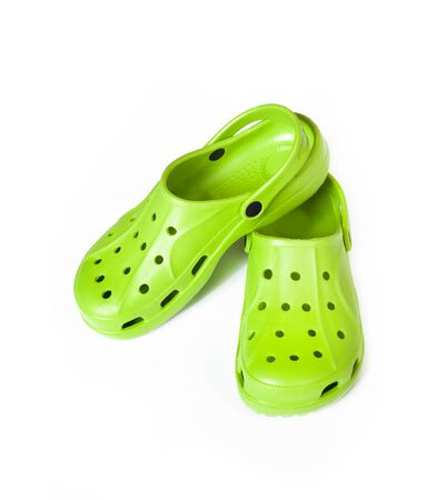 Pair of bright green rubber clogs isolated on white background