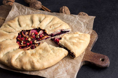 Homemade galette with apples, elder berries and walnuts decorated with fresh cowberry on rustic dark background Stock fotó