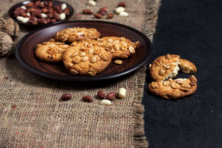 Homemade peanut cookies on a brown plate with raw peanuts in background. Rustic style food