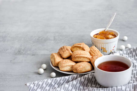 Tasty breakfast. Homemade sweet cinnamon cookies and cup of tea. Apple confiture on background. Copy space