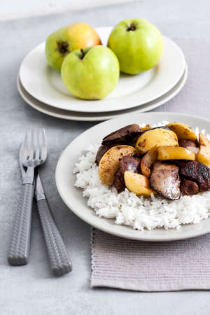 Fried chicken liver with apples served with white rice on a plate. Green apples on background