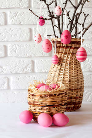 Easter composition with decorated tree branches in a wicker vase and pink colored eggs in wicker basket on white background. Copy space