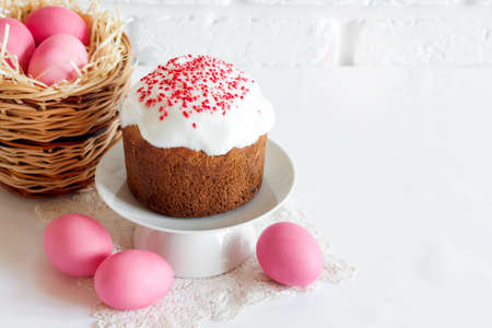 Minimalistic Easter composition with wicker basket with pink colored eggs and Easter cake on white background. Copy space Stock fotó