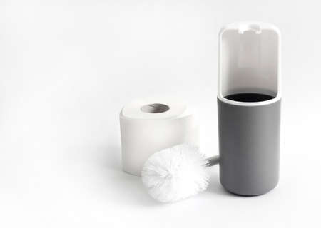 White and gray plastic toilet brush and roll of toilet paper on white background. Copy space