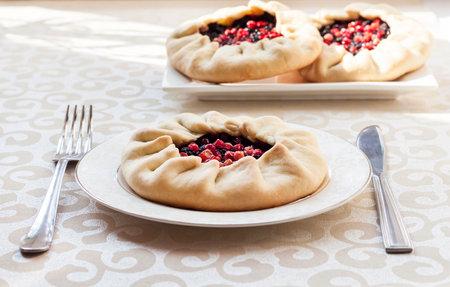 Tasty breakfast. Homemade sweet galette with elderberries and cowberries on a plate