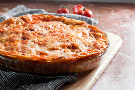 Homemade baked lasagna in round glass baking dish on wooden board Stock fotó
