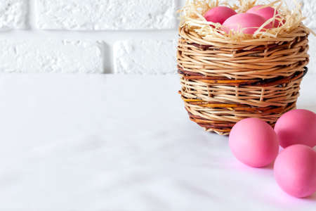 Minimalistic Easter composition with wicker basket and pink colored eggs on white background. Copy space