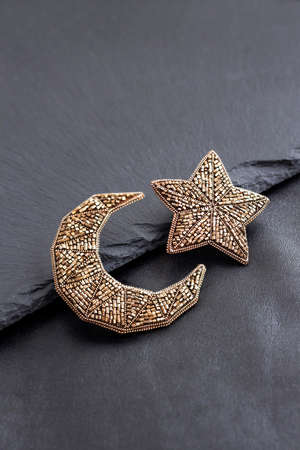 Seed beads embroidered brooches in a shape of Moon and star on black background Stock fotó