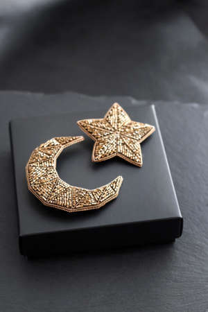 Seed beads embroidered brooches in a shape of Moon and star on black box background Stock fotó