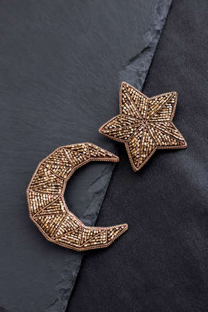 Seed beads embroidered brooches in a shape of Moon and star on black background. Flat lay