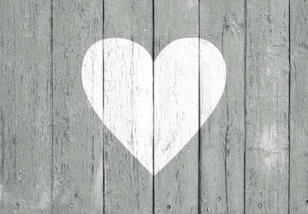 Old wooden board background with cracked gray paint and white heart shape. Valentine's day and love concept