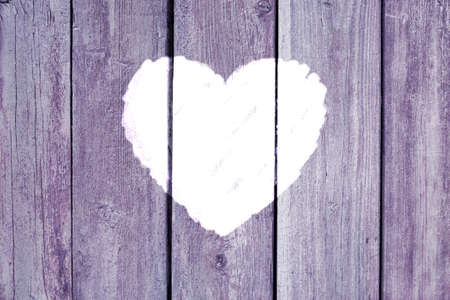 Old wooden board background with cracked lavender paint and white heart shape. Valentine's day and love concept