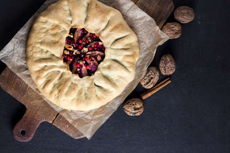 Sweet galette pie with apples, elder berries and walnuts decorated with fresh cowberry on dark background. Top view, flat lay. Copy space