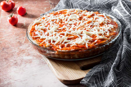Homemade lasagna ready for baking in round glass baking dish on wooden board