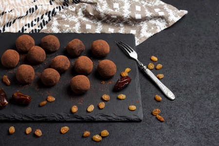 Homemade vegan truffles with dried fruits, walnuts and raw cocoa powder served on black slate plate. Copy space