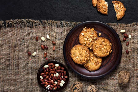 Homemade peanut cookies on a brown plate with raw peanuts in background. Rustic style food. Flat lay, top view Stock fotó