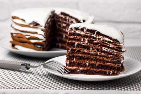 Homemade chocolate cake with cream. Slice of cake on a plate