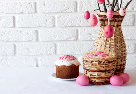 Easter composition with decorated tree branches in a wicker vase, pink colored eggs in wicker basket and Easter cake on white background. Copy space