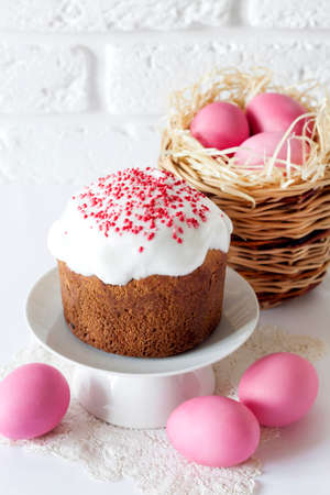 Minimalistic Easter composition with wicker basket with pink colored eggs and Easter cake on white background