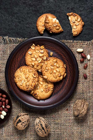 Homemade peanut cookies on a brown plate with raw peanuts in background. Rustic style food. Flat lay, top view 版權商用圖片
