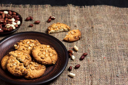 Homemade peanut cookies on a brown plate with raw peanuts in background. Rustic style food. Copy space 版權商用圖片