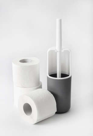 White and gray plastic toilet brush and roll of toilet paper on white background 版權商用圖片