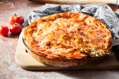 Homemade baked lasagna in round glass baking dish on wooden board 版權商用圖片